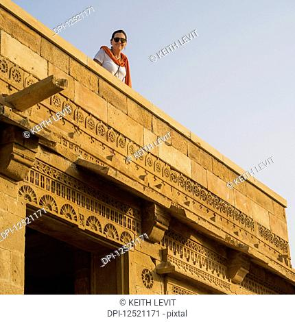 A female tourist looks down from a rooftop in the abandoned village of Kuldhara in the Jaisalmer district, having a reputation of being haunted; Jiyai