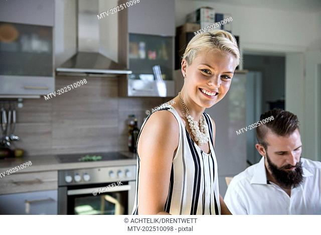 Portrait of a young woman in the kitchen and man in the background, Bavaria, Germany