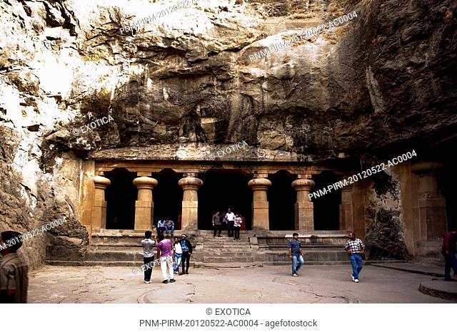 Tourists at the entrance of a cave, Elephanta Caves, Elephanta Island, Mumbai, Maharashtra, India