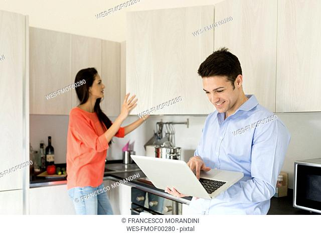 Smiling young man with woman in kitchen using laptop