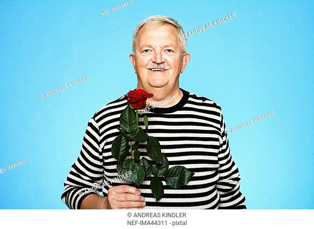 A gentleman holding a red rose