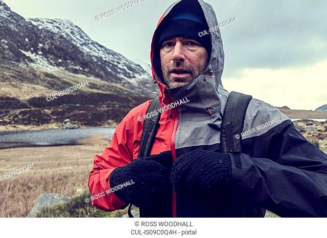 Male hiker with hood up in snow capped mountain landscape, portrait, Llanberis, Gwynedd, Wales
