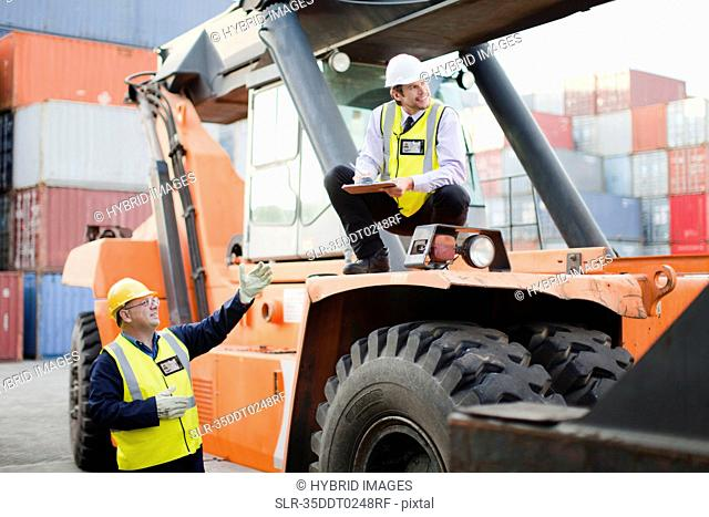 Workers on machinery in shipping yard