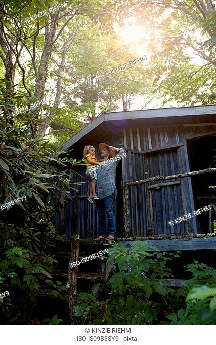 Mother and daughter standing outside wooden cabin