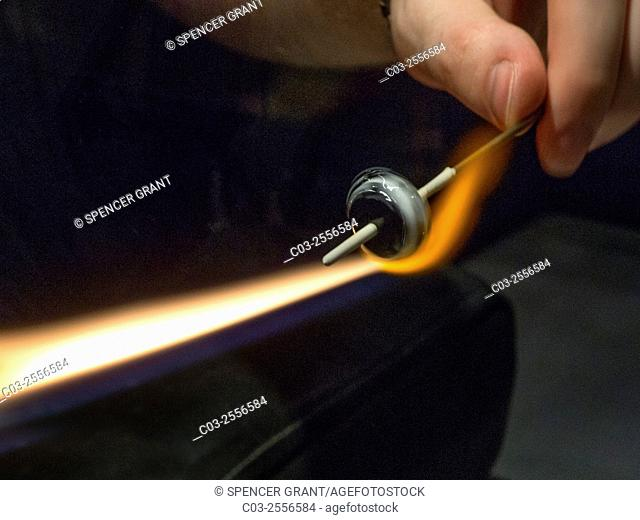 Using a hot gas flame, a craftsman adds details to a decorative glass bead
