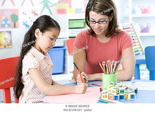 A teacher and a girl drawing