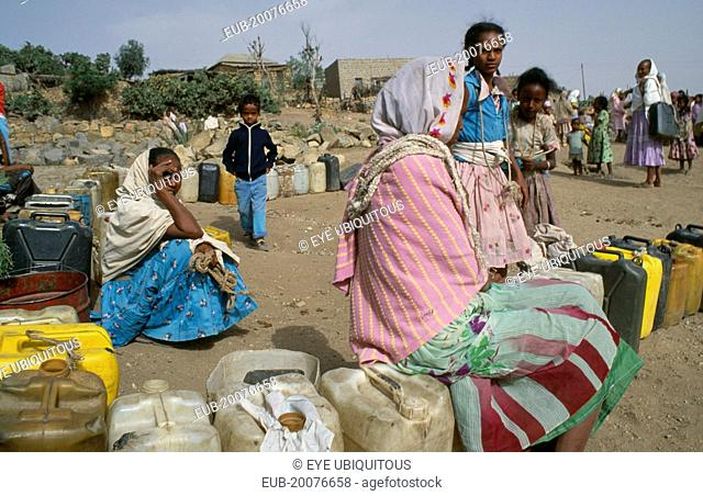 Women and children waiting at water point in provincial town