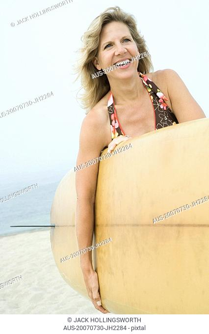 Portrait of a mature woman holding a surfboard and smiling