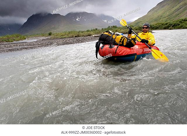 Man packrafting the Sanctuary River in rainy weather, Denali National Park & Preserve, Alaska Range, Interior Alaska, Summer