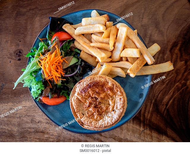 Typical Australian pub meal a meat pie with salad and fries