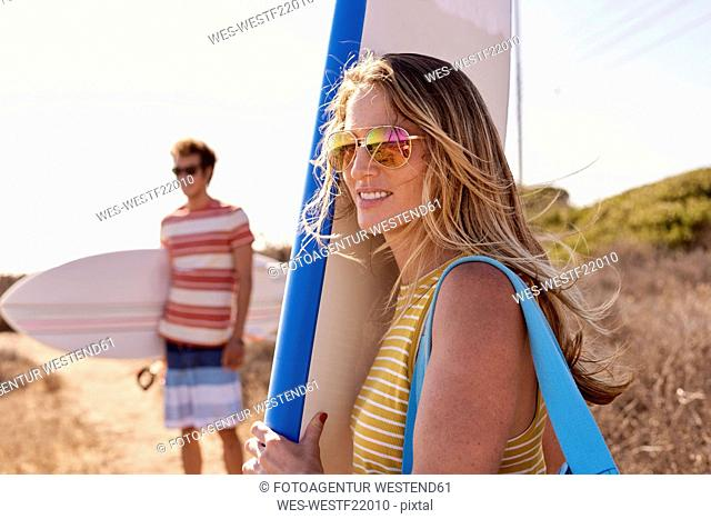 Couple carrying surfboards looking at view