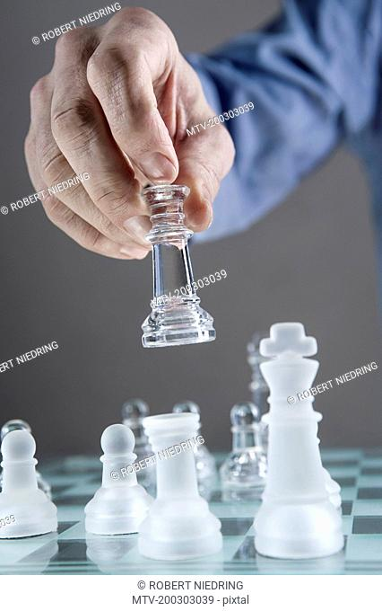 Close-up of man's hand going for checkmate while playing chess, Bavaria, Germany