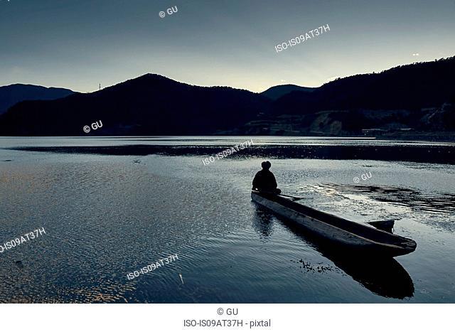 Silhouette of mountain range with man in boat, Luga Lake, Yunnan, China