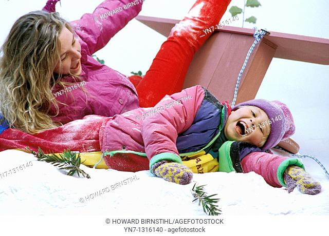 mother and daughter enjoying crashing their sled in the snow