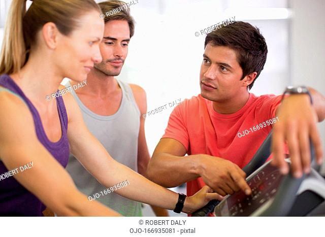 Men helping woman with treadmill in gymnasium