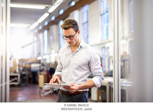 Young businessman in factory using tablet