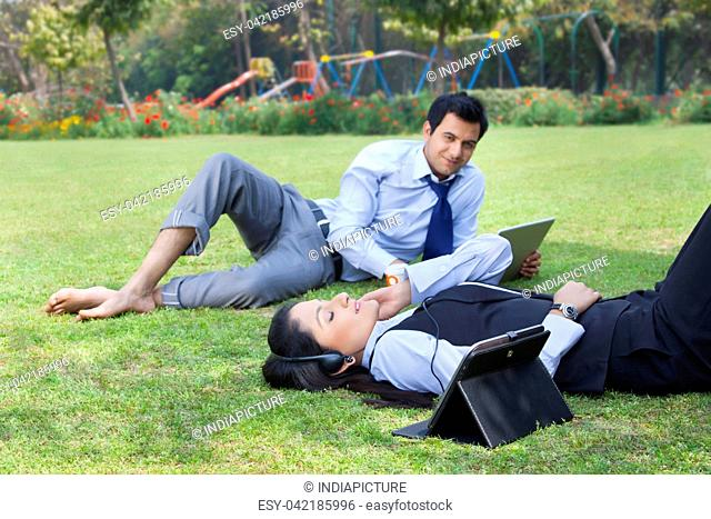Businessman working in the park while businesswoman relaxes