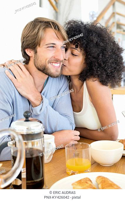 Woman kissing her husband at a dining table