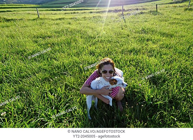 Young woman hugging her small dog in the fields of Niembro, Asturias, Spain