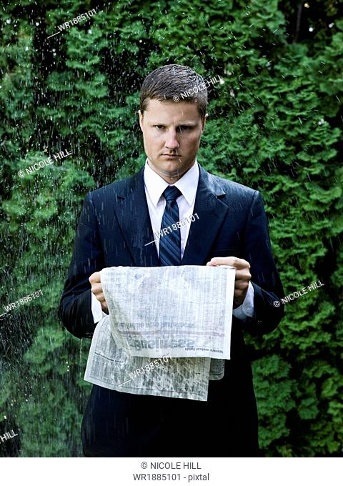 man in a suit standing next to a sprinkler reading the paper
