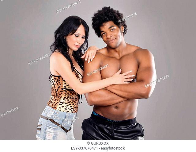 Young and sexy passionate couple on gray studio background