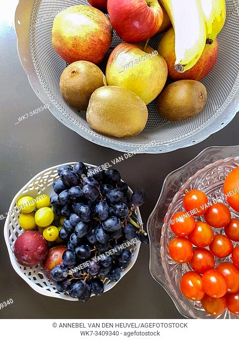 Healthy and fresh various fruit in a bowl on the table top view, grapes, apples, bananas healthy lifestyle colorful
