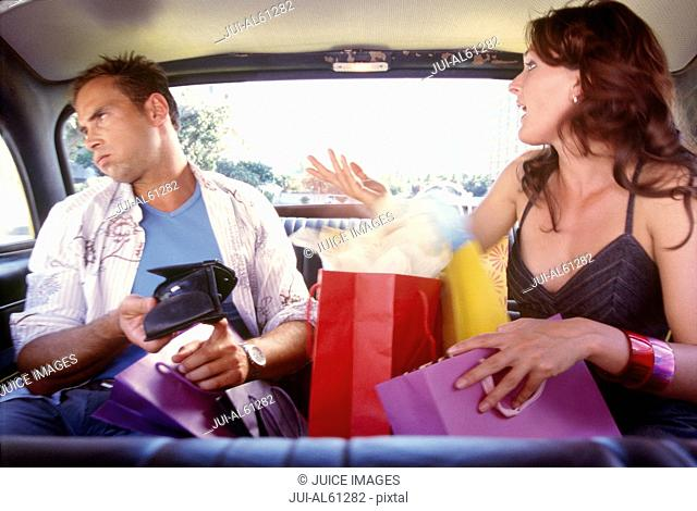 Young couple arguing in back seat of taxi