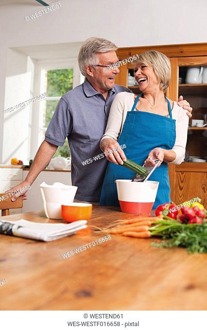 Germany, Kratzeburg, Senior couple preparing food, smiling