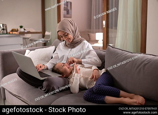 Happy Muslim mother playing with daughter during work