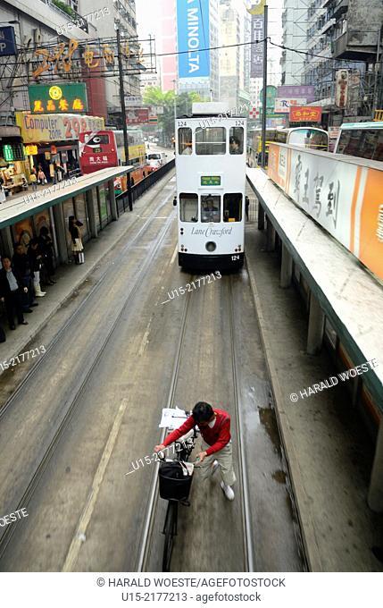 Hong Kong, China, Asia. Cyclist followed by tram pushing bicycle along tram rails on Hong Kong Island