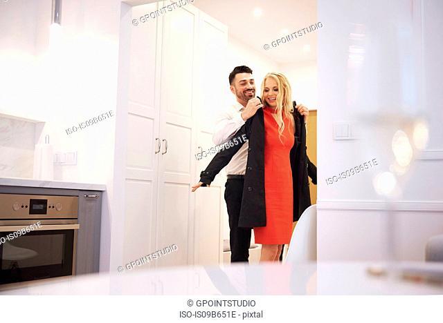 Man taking woman's coat