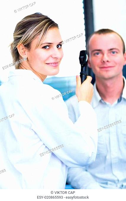 Optometry concept - handsome young man having his eyes examined by an eye doctor (color toned image shallow DOF)