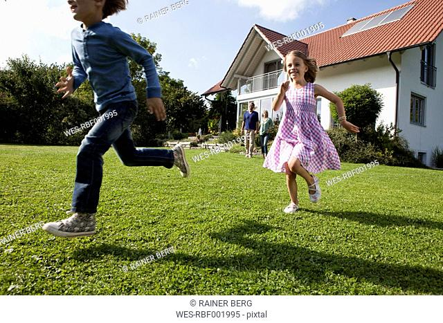 Brother and sister running in garden