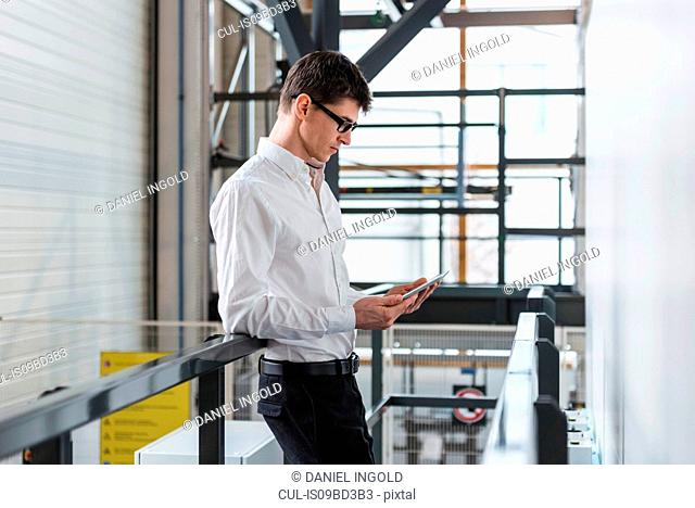 Young man standing in factory, using digital tablet