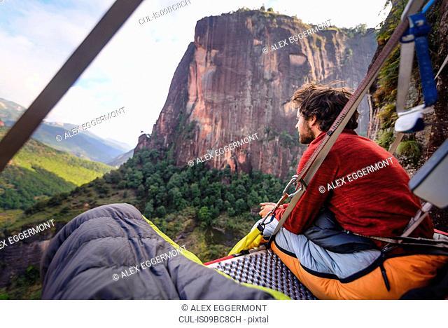 Rock climber on portaledge, looking at view, Liming, Yunnan Province, China