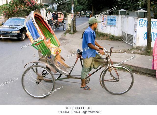 Cycle Rickshaw Rider Riding empty Vehicle on street at Dhaka ; Bangladesh