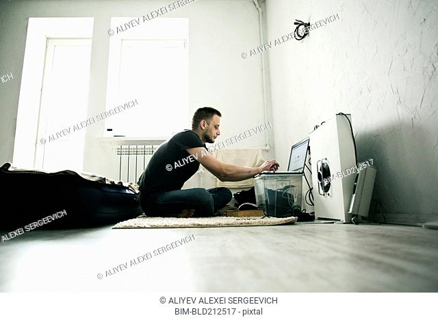 Caucasian man using laptop in bedroom