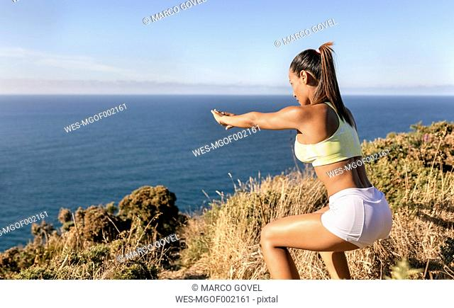 Spain, Asturias, sportswoman on the coast, knee bend