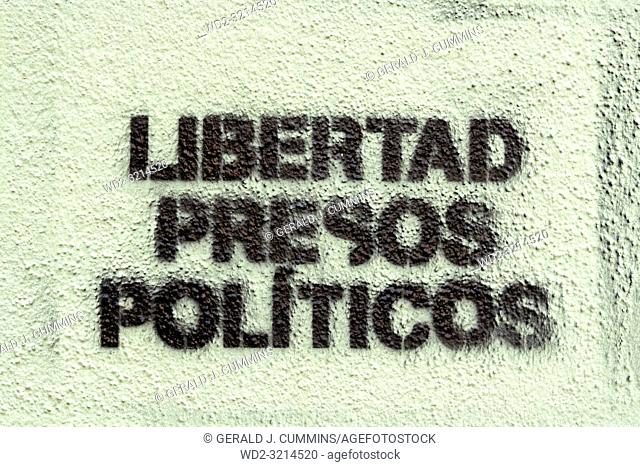 Political graffiti, in the Catalan language, stenciled onto the ground. calling for freedom for political prisoners. in the town of Figueres