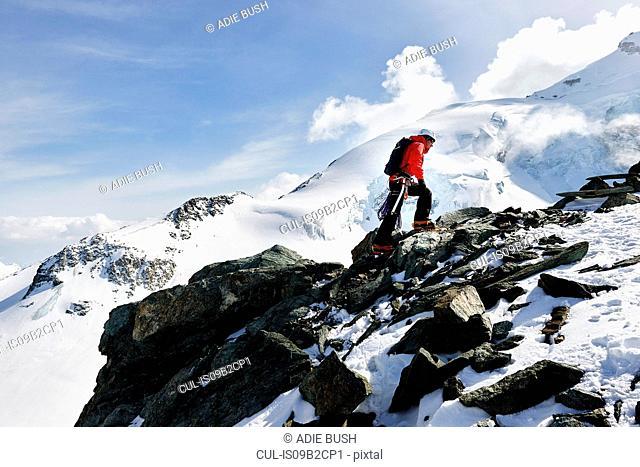 Man climbing up snow covered mountain, Saas Fee, Switzerland