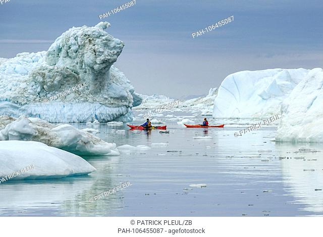 21.06.2018, Gronland, Denmark: Two tourists are paddling on the ocean between large icebergs off the coastal town of Ilulissat in western Greenland
