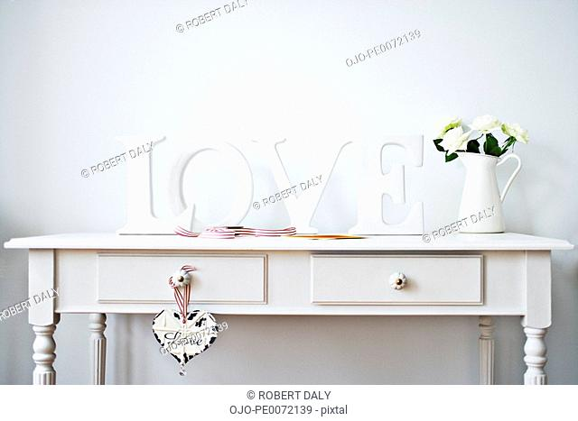 Love decorations, ribbon, roses and card on desk