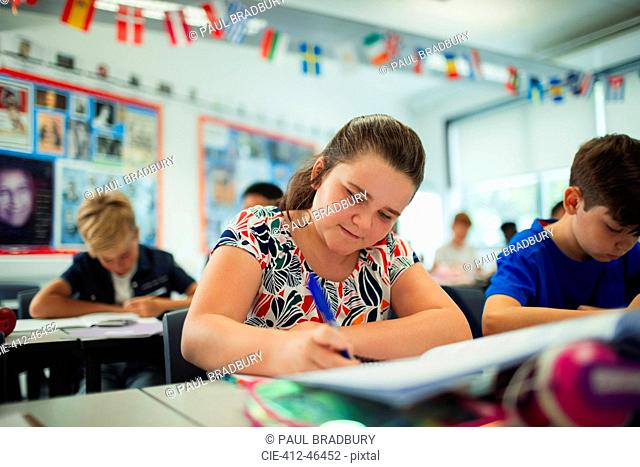 Focused junior high school girl student doing homework in classroom