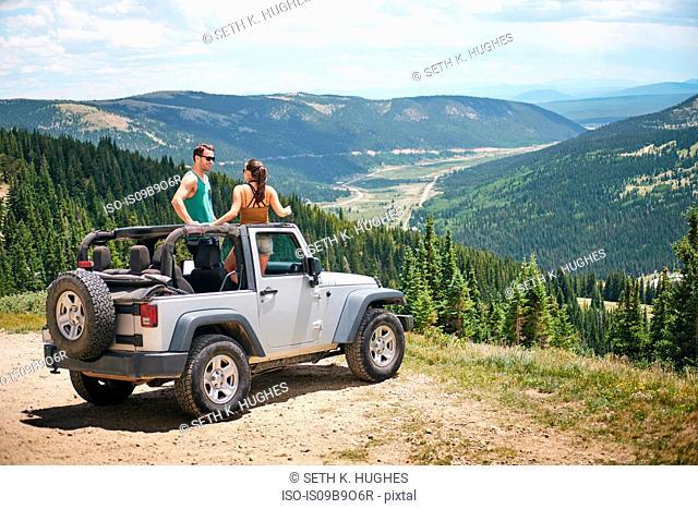 Road trip couple in parked four wheel convertible in Rocky mountains, Breckenridge, Colorado, USA
