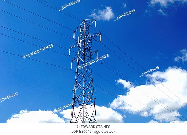 England, Buckinghamshire, West Wycombe, Electricity pylon with clouds and blue sky. Pylons can be made from a number of materials including wood, concrete