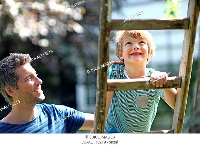Father helping son to climb ladder