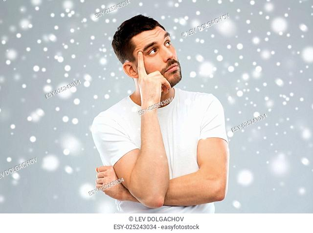 doubt, expression, winter, christmas and people concept - man thinking over snow on gray background