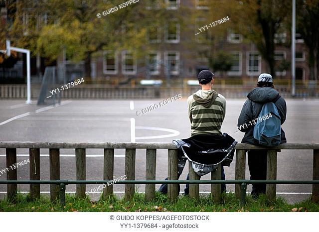 Rotterdam, Netherlands. Two friends having a private conversation on a courtyard
