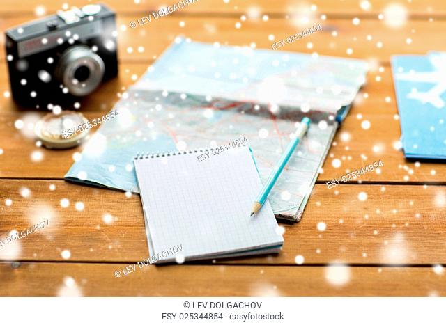 vacation, tourism, travel, winter holidays and objects concept - close up of blank notepad with map and airplane tickets