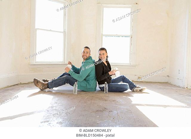 Mixed race couple sitting on floor of new home